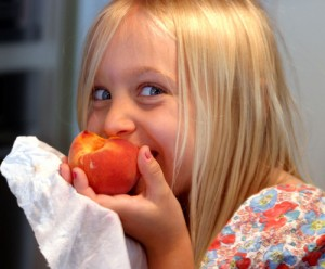 Girl enjoying peach on the low oxalate diet.